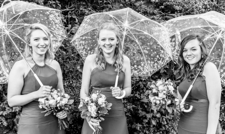 Bridesmaids with umbrellas by Highland Wedding Photographer Ewan Mathers
